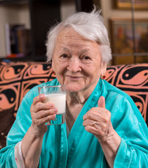 Old woman holding a glass milk
