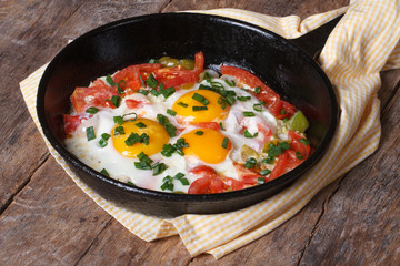 Fried eggs with tomatoes and onions in a pan