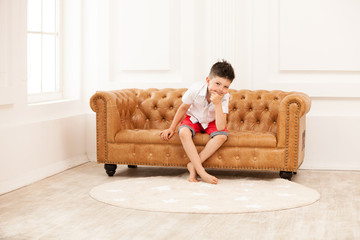 Young boy looking pensively while sitting on couch at home