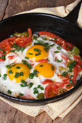 Fried eggs with tomatoes, peppers and onions in a pan