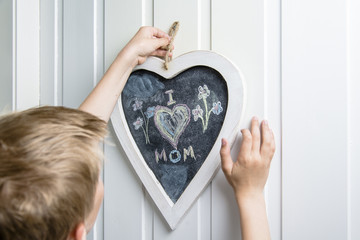 Boy hanging up a heart shaped blackboard with I love mom