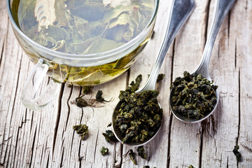 cup of green tea and spoons