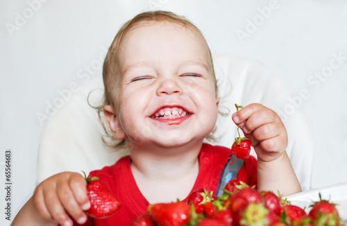 happy toddler boy eating strawberries - 65564683