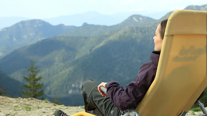 Young woman relaxing in the mountains enjoying valley view