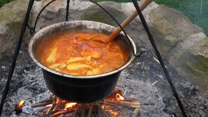 Stirring traditional Hungarian paprika potatoes on a campfire