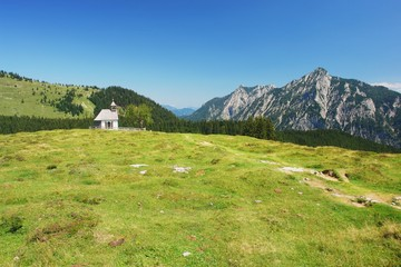 View of meadow with a church in Postalm, Austrian Alps