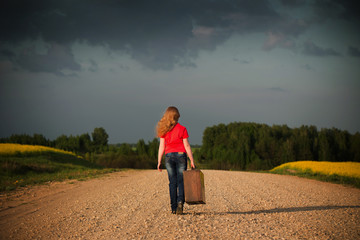 little girl holding a suitcase on a country road