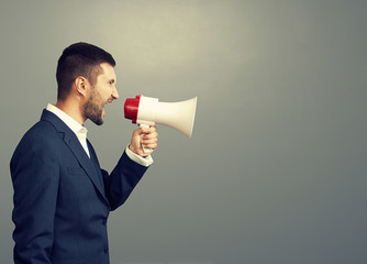 angry businessman using megaphone
