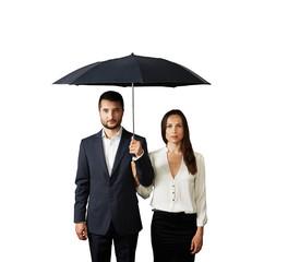 serious couple under umbrella