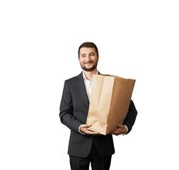 smiley businessman holding paper bag