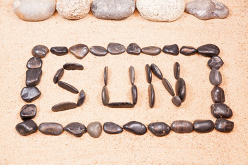 word sun written with pebbles on the sand of a beach