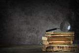Pile of old antique and yellowed books with a magnifying glass - 65567639