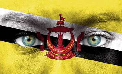 Human face painted with flag of Brunei