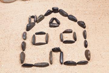 maison dessinée avec des galets sur le sable d'une plage