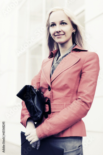 Young fashion business woman against office building
