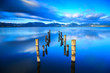 Wooden pier or jetty remains on a blue lake sunset and sky refle