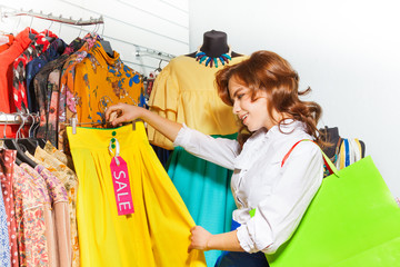 Excited girl chooses yellow skirt during sale