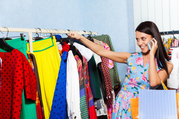 Young woman looking at chosen clothes with mobile