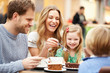 Family Enjoying Snack In Café Together - 65571207