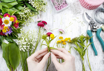 Florist at work. Woman making bouquet of wild flowers