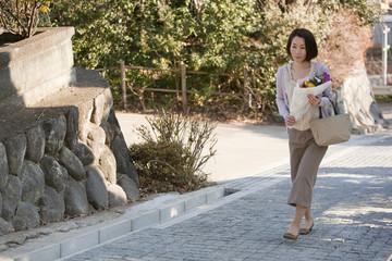 坂を上りお墓参りに向かう花を持った女性