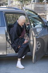 車から降りる僧侶