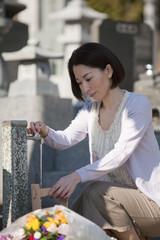 お墓参りのため水桶で水を汲む女性