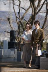 花と水桶を持ち墓地を歩く夫婦