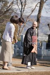 墓地で話す夫婦と僧侶