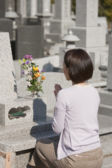 お墓の前で手を合わせる女性の後姿