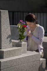 お墓の前で手を合わせる女性