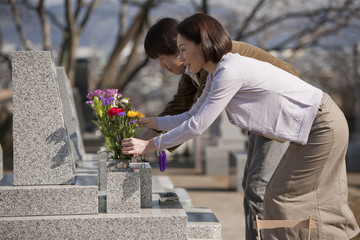 お墓に花を供える夫婦
