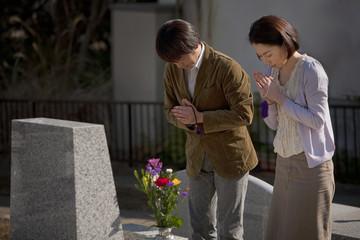 お墓の前で手を合わせる夫婦