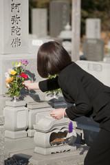 お墓に花を供える喪服姿の女性の後姿