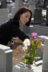 お墓に花を供える喪服姿の女性