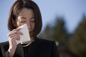 ハンカチで涙を拭う喪服姿の女性