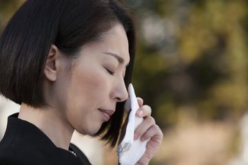 ハンカチで涙を拭う喪服姿の女性の横顔