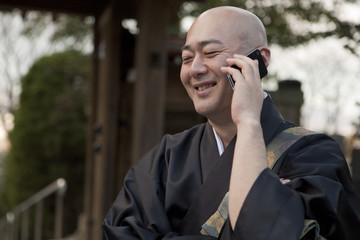 スマートフォンを使用する笑顔の僧侶