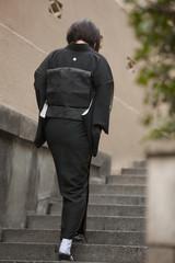 階段を登る喪服姿の女性の後姿