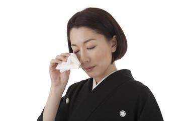 ハンカチで涙を拭う喪服姿の女性 斜め