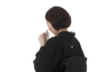 ハンカチで涙を拭う喪服姿の女性 後ろ斜め