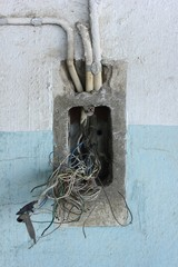 Messy cables on a wall. Broken electricity plug.