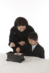 焼香をする喪服姿の母親と少年 斜め