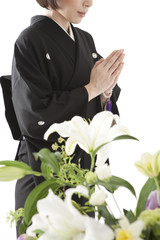 喪服姿で合掌する女性と祭壇の花