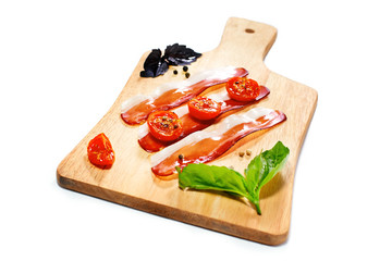 Dried cherry tomatoes with bacon served on carving board.