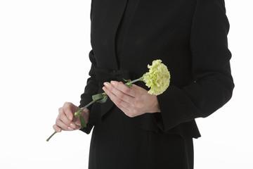 一輪の花を持った喪服姿の女性の手