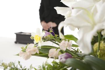 焼香台の前に立つ喪服姿の女性と祭壇の花