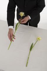 チューリップの花を手向ける喪服姿の男性