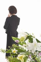 合掌する喪服姿の女性の後姿と祭壇の花