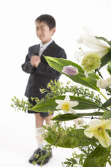 手を組み目を閉じる喪服姿の少年と祭壇の花